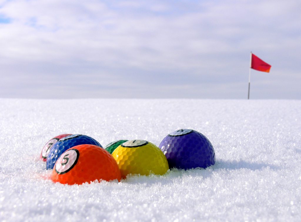 Golfballs lined up as colorful biljardballs on a snowcovered green area